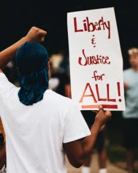 Image of man holding Liberty and Justice for All sign